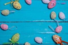 Fondo de Pascua Huevos de Pascua adornados multicolores, polvo multicolor en un fondo de la turquesa Espacio libre Imagen de archivo libre de regalías