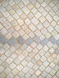 Fondo de pavimentación inclinado de la calle de las piedras del adoquín Foto de archivo