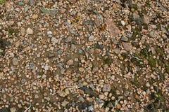 Fondo de pequeñas piedras coloreadas en la arena fotos de archivo