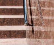 Fondo de piedra de los pasos de las escaleras del granito con la manija de aluminio metálica Escaleras modernas rojo marrón imagenes de archivo