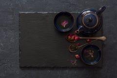 Fondo de piedra negro con las tazas de infusión de hierbas Fotos de archivo