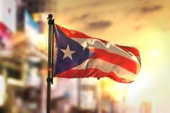 Fondo de Puerto Rico Flag Against City Blurred en la parte posterior de la salida del sol fotografía de archivo