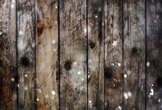 Fondo de tableros de madera con nieve y efecto del bokeh del brillo Foto de archivo libre de regalías