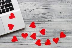 Fondo de una tarjeta del día de San Valentín en una tabla de madera con un ordenador portátil y él foto de archivo libre de regalías
