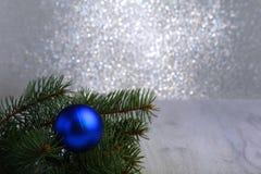 Fondo decorativo con las ramas del abeto y las bolas azules en la plata Concepto del día de fiesta de la tarjeta de Navidad fotografía de archivo libre de regalías