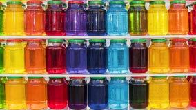 Fondo dei barattoli di vetro con di liquido colorato multi Fotografie Stock Libere da Diritti