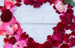 Fondo dei biglietti di S. Valentino, cuore di legno, petali di rose, amore di giorno di S. Valentino Fotografia Stock