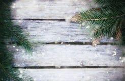 Fondo dei bordi di legno con i rami di pino in precipitazioni nevose Immagini Stock