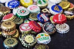 Fondo dei cappucci della bottiglia di birra, una miscela di varie marche globali immagine stock