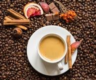 Fondo dei chicchi di caffè con la tazza, la cannella ed il cioccolato di cofee Immagine Stock