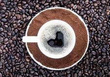 Fondo dei chicchi di caffè e di una tazza di caffè Immagine Stock