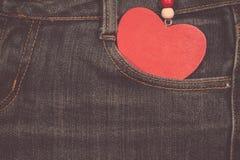 Fondo dei jeans con cuore di legno Giorno del biglietto di S Immagine Stock