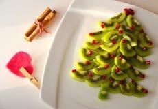 Fondo del Año Nuevo del árbol de navidad del kiwi y de la granada Idea sana del postre para el partido de los niños Imagen de archivo libre de regalías