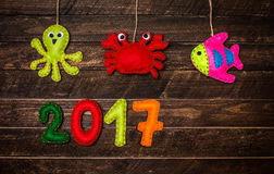 Fondo del Año Nuevo con los juguetes hechos a mano de la Navidad hechos del fieltro encendido Imagen de archivo