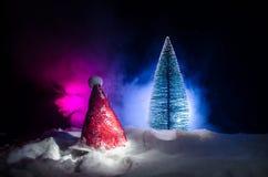 Fondo del Año Nuevo del día de fiesta de la Navidad con el sombrero de Papá Noel y el árbol de navidad borroso en fondo nevoso Añ Imagen de archivo libre de regalías