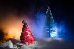 Fondo del Año Nuevo del día de fiesta de la Navidad con el sombrero de Papá Noel y el árbol de navidad borroso en fondo nevoso Añ Fotos de archivo