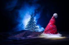 Fondo del Año Nuevo del día de fiesta de la Navidad con el sombrero de Papá Noel y el árbol de navidad borroso en fondo nevoso Añ Imágenes de archivo libres de regalías