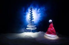 Fondo del Año Nuevo del día de fiesta de la Navidad con el sombrero de Papá Noel y el árbol de navidad borroso en fondo nevoso Añ Fotografía de archivo libre de regalías