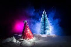 Fondo del Año Nuevo del día de fiesta de la Navidad con el sombrero de Papá Noel y el árbol de navidad borroso en fondo nevoso Añ Foto de archivo