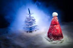 Fondo del Año Nuevo del día de fiesta de la Navidad con el sombrero de Papá Noel y el árbol de navidad borroso en fondo nevoso Añ Fotos de archivo libres de regalías