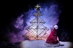 Fondo del Año Nuevo del día de fiesta de la Navidad con el sombrero de Papá Noel y el árbol de navidad borroso en fondo nevoso Añ Foto de archivo libre de regalías