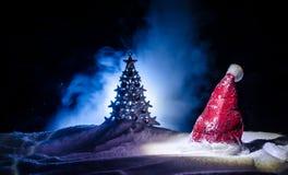 Fondo del Año Nuevo del día de fiesta de la Navidad con el sombrero de Papá Noel y el árbol de navidad borroso en fondo nevoso Añ Imagenes de archivo