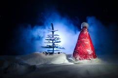 Fondo del Año Nuevo del día de fiesta de la Navidad con el sombrero de Papá Noel y el árbol de navidad borroso en fondo nevoso Añ Imagen de archivo