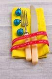 Fondo del Año Nuevo de la Navidad fije la bifurcación, cuchillo, cuchara en servilleta amarilla con la cinta del oro del día de f Fotos de archivo