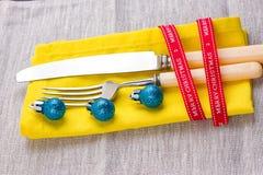Fondo del Año Nuevo de la Navidad fije la bifurcación, cuchillo, cuchara en servilleta amarilla con la cinta del oro del día de f Fotografía de archivo