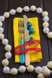 Fondo del Año Nuevo de la Navidad fije la bifurcación, cuchillo, cuchara en servilleta amarilla con la cinta del oro del día de f Imagen de archivo