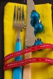 Fondo del Año Nuevo de la Navidad fije la bifurcación, cuchillo, cuchara en servilleta amarilla con la cinta del oro del día de f Fotos de archivo libres de regalías