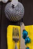 Fondo del Año Nuevo de la Navidad fije la bifurcación, cuchillo, cuchara en servilleta amarilla con la cinta del oro del día de f Imagenes de archivo