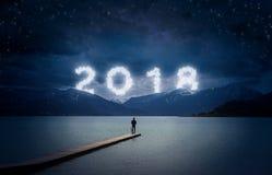 Fondo del Año Nuevo, hombre joven colocándose en un embarcadero en un lago y Foto de archivo