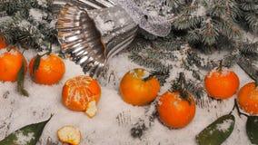 Fondo del Año Nuevo mandarinas, nieve, abeto en un fondo de madera Fotografía de archivo