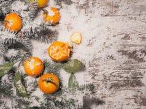 Fondo del Año Nuevo mandarinas, nieve, abeto en un fondo de madera Imagen de archivo libre de regalías