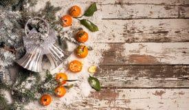 Fondo del Año Nuevo mandarinas, nieve, abeto en un fondo de madera Foto de archivo libre de regalías