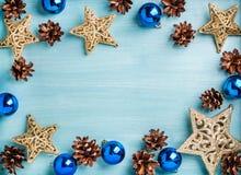 Fondo del Año Nuevo o de la Navidad: estrellas de oro, bolas de cristal azules y conos sobre el contexto de madera de la turquesa Imagen de archivo