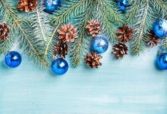 Fondo del Año Nuevo o de la Navidad: ramas del abeto, bolas de cristal azules y conos del pino sobre el contexto de madera de la  Imagenes de archivo