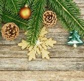 Fondo del Año Nuevo o de la Navidad: ramas del abeto, bolas de cristal coloridas y copo de nieve de oro, conos sobre el viejo con Foto de archivo libre de regalías