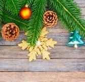 Fondo del Año Nuevo o de la Navidad: ramas del abeto, bolas de cristal coloridas y copo de nieve de oro, conos sobre el viejo con Imagen de archivo libre de regalías