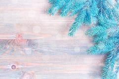 Fondo del Año Nuevo y de la Navidad Ramas de árbol azules de abeto con los copos de nieve en el fondo de madera Fotografía de archivo