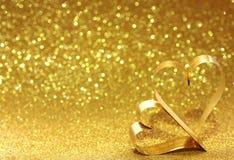 Fondo del amarillo del brillo del día del ` s de la tarjeta del día de San Valentín y dos corazones del oro fotos de archivo