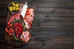 Fondo del Antipasto Surtido de bocados de la carne en el tablero con las aceitunas y el parmesano fotos de archivo