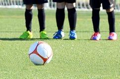 Fondo del balón de fútbol con las piernas de los jugadores Fotografía de archivo