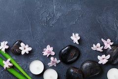 Fondo del balneario con el guijarro del masaje, las hojas verdes, las flores hermosas y las velas en la opinión de sobremesa de p Imagen de archivo