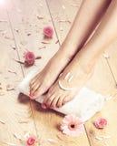 Fondo del balneario con los pies, las flores y los pétalos hermosos Foto de archivo libre de regalías
