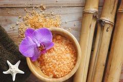 Fondo del balneario en una tabla de madera con el bambú, la sal de baño, la estrella de mar y la toalla suave Foto de archivo libre de regalías