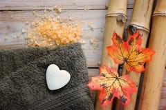 Fondo del balneario en una tabla de madera con el bambú, la sal de baño, las hojas de otoño y la toalla Imágenes de archivo libres de regalías