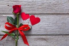 Fondo del biglietto di S. Valentino con il fiore della rosa rossa, cuori di carta su legno rustico Fotografie Stock