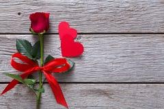 Fondo del biglietto di S. Valentino con il fiore della rosa rossa, cuori di carta su legno rustico Immagini Stock